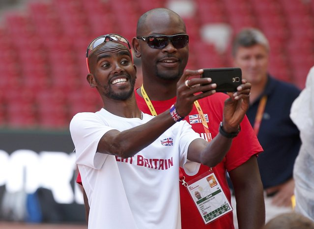 Mo Farah of Great Britain poses for a selfie with a team doctor inside the Bird's Nest Stadium at the Wold Athletics Championships in Beijing, China, August 21, 2015. (Photo by Phil Noble/Reuters)