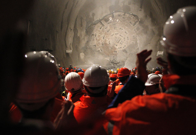 "Miners watch as the drill machine ""Sissi"" breaks through the rock at the final section Faido-Sedrun construction site of the NEAT Gotthard Base Tunnel October 15, 2010. (Photo by Christian Hartmann/Reuters)"