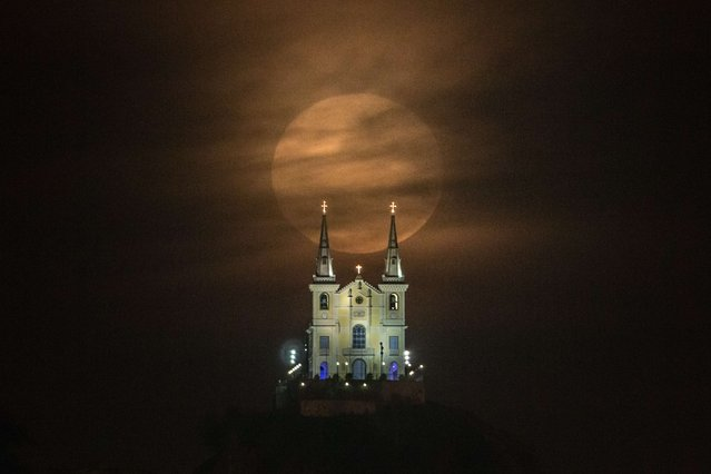 The full moon descends behind the Nossa Senhora da Penha Church in Rio de Janeiro, Brazil, on August 10, 2014. In this time of the year the orb is at the closest point to the earth. Experts name this phenomenon the supermoon or perigee. (Photo by Yasuyoshi Chiba/AFP Photo)