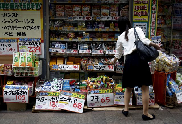 A shopper looks at items outside a discount drug store at a shopping district in Tokyo, Japan, July 29, 2015. (Photo by Yuya Shino/Reuters)
