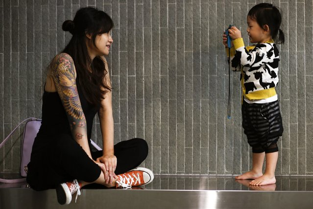 A visitor poses a photo for her daughter at the International Hong Kong China Tattoo Convention in Hong Kong August 22, 2014. The territory held its second international tattoo convention on Friday, hoping to pin Hong Kong onto the global tattoo-map and aiming at changing the perception of tattoos in a city where inked skin is still strongly associated with triads and criminals. (Photo by Bobby Yip/Reuters)