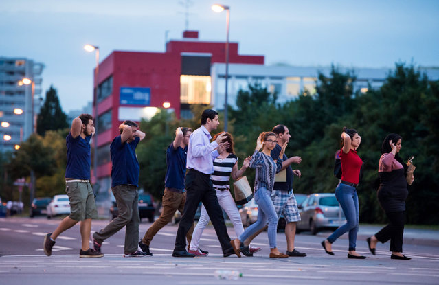 Evacuated people from the shopping mall (the Olympia Einkaufzentrum (OEZ) walk with their hands raised in Munich on July 22, 2016 following a shooting earlier. At least one person has been killed and 10 wounded in a shooting at a shopping centre in Munich on Friday, German police said. (Photo by AFP Photo/Stringer)