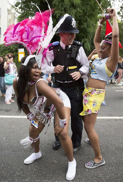 Performers dance with a police officer in the children's day parade at the Notting Hill Carnival in London August 24, 2014. (Photo by Neil Hall/Reuters)