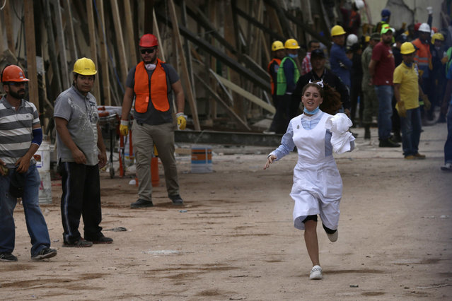 A nurse runs during rescue efforts at the Enrique Rebsamen school in Mexico City, Mexico, Wednesday, September 20, 2017. Thousands of professionals and volunteers are working frantically at dozens of wrecked buildings across the capital and nearby states looking for survivors of the powerful quake that hit Tuesday. (Photo by Marco Ugarte/AP Photo)