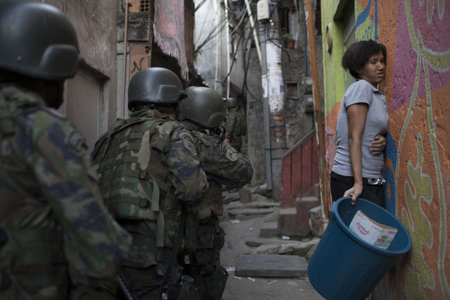 Woman squeezes against the wall as soldiers patrol in an alley during an operation in Rocinha slum in Rio de Janeiro, Brazil, Friday, September 22, 2017. Shootouts erupted in several areas of Rio de Janeiro on Friday, prompting Brazilian authorities to shut roads, close schools and ask for the Army to intervene. (Photo by Leo Correa/AP Photo)