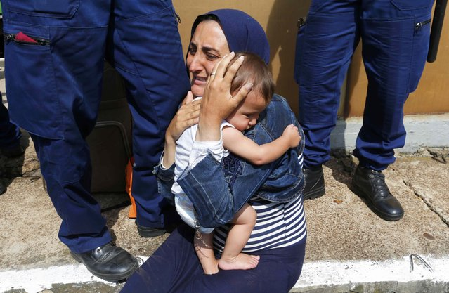 Hungarian policemen stand by a migrant holding a baby at the railway station in the town of Bicske, Hungary, September 3, 2015. (Photo by Laszlo Balogh/Reuters)