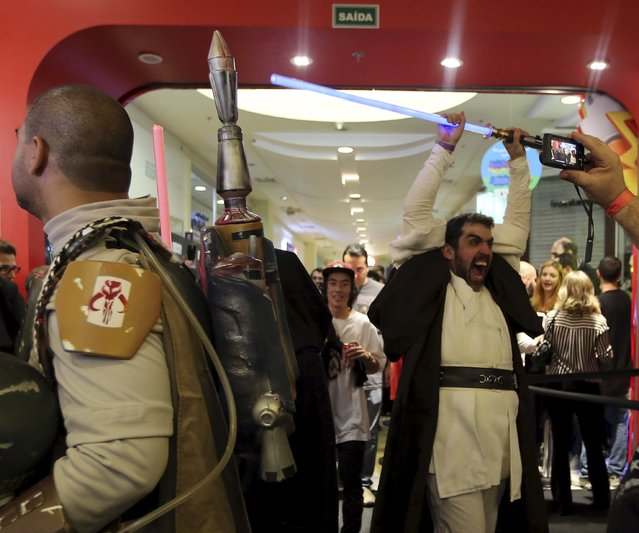 """A man dressed as Obi-Wan Kenobi (R) reacts as he enter in a store to buy new toys from the upcoming film """"Star Wars: The Force Awakens"""" on """"Force Friday"""" in Sao Paulo, Brazil, September 4, 2015. (Photo by Paulo Whitaker/Reuters)"""