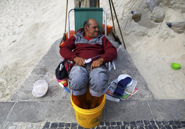 2016 Rio Olympics, Olympic Park on July 29, 2016. A man listens to the radio as he sits with his feet in a bucket of water. (Photo by Ivan Alvarado/Reuters)