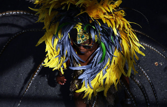 A mas band member walks under a pedestrian bridge along the parade route at the Toronto Caribbean Carnival's grand parade, in Toronto on Saturday, July 30, 2016. (Photo by Cole Burston/The Canadian Press via AP Photo)