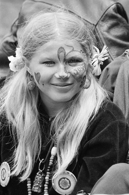 In this Thursday, June 21, 1967 file photo, Judy Smith, wearing face paint and flowers in her hair, smiles as she and others gather at Golden Gate Park in San Francisco. Fifty years ago, throngs of American youth descended on San Francisco to join a cultural revolution. (Photo by Robert W. Klein/AP Photo)