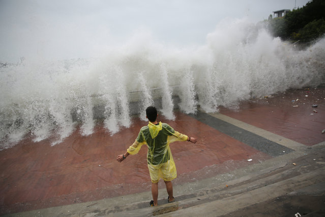A man stands near waves at a port as Typhoon Nida lands in Shenzhen, Guangdong Province, China, August 2, 2016. (Photo by Reuters/Stringer)