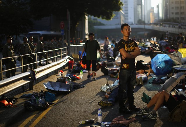 A protester stands as he blocks the main street to the financial Central district, outside the government headquarters in Hong Kong, September 29, 2014. (Photo by Carlos Barria/Reuters)