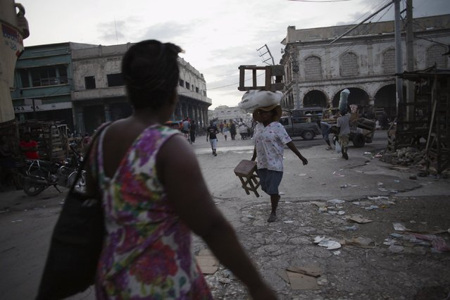A saleswoman walks carrying stools and goods at dusk in a street in Port-au-Prince, Haiti, March 7, 2016. (Photo by Andres Martinez Casares/Reuters)