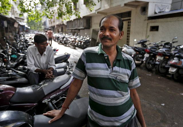 Sunilkumar Rajput, an unemployed craftsman, stands outside a diamond polishing and processing unit where he used to work, at Surat in Gujarat, India, August 31, 2015. Rajput spent 25 years cutting gems in this coastal city, where streets are lined with workshops of all sizes, bustling with craftsmen huddled under desk lamps, preparing to carve rough diamonds into multi-faceted gems. He lost his job in June. (Photo by Amit Dave/Reuters)