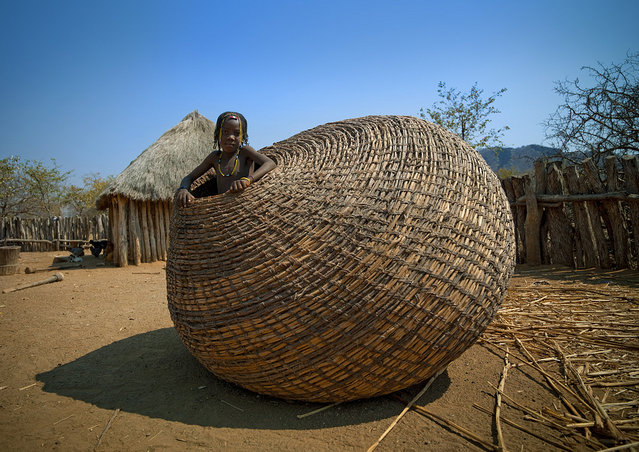 """Mundimba tribe girl in giant basket – Angola. Those giant baskets are used to keep the grains in Mundimba tribe, in south Angola"". (Eric Lafforgue)"