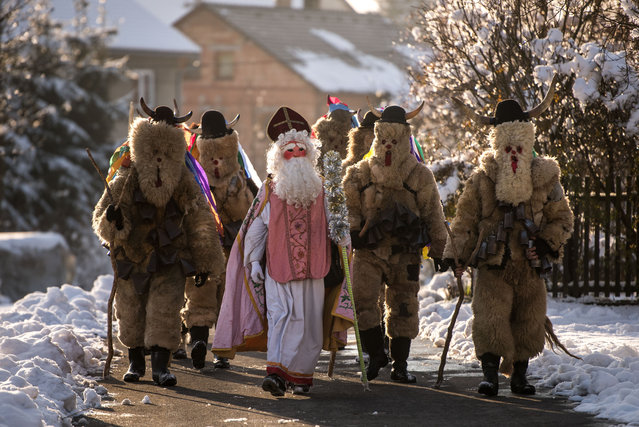 A participant Saint Nicholas parade walks from house to house dressed in the traditional devil and Nicholas costumes in Francova Lhota district of Zlin, Czech Republic on December 3, 2017. This type of parade is one of the most popular age old tradition in a few villages in Wallachia region (eastern part of Czech Republic). Saint Nicholas walks the streets going from house to house three days and Saint Nicholas gives sweets to children and the devils get up to mischief. (Photo by Lukas Kabon/Anadolu Agency/Getty Images)