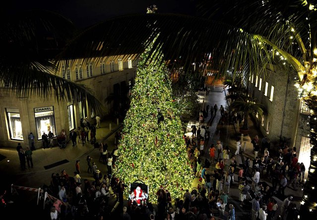 Santa Claus greets visitors as a large Christmas tree towers over Worth Avenue in Palm Beach. (Photo by Chris Salata/The Palm Beach Daily News)