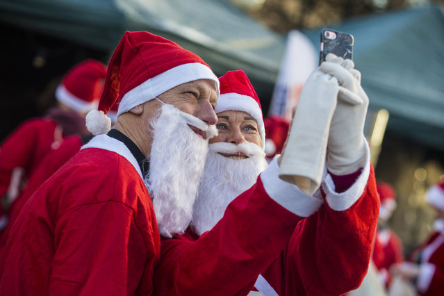 Participants in the Stockholm Santa Run take a selfie at Kungstradgarden on December 10, 2017 in Stockholm, Sweden. The Stockholm Santa Run is an annual event where participants dress as Santa Claus and run or walk through a course in the city centre raising money for charity. (Photo by Michael Campanella/Getty Images)