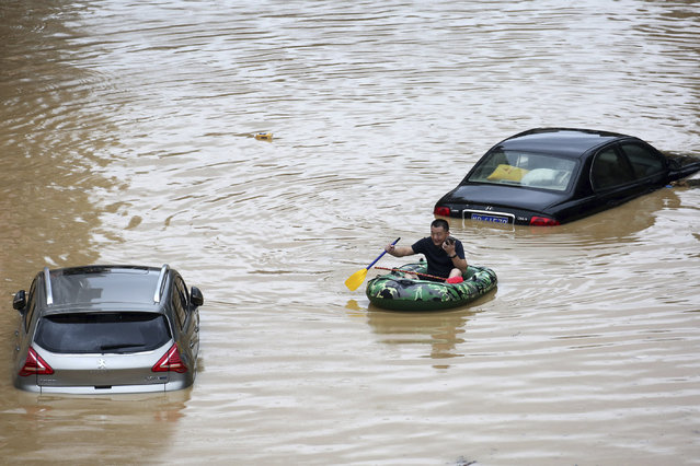 In this photo released by Xinhua News Agency, a man paddles with an inflatable boat past submerged cars during a flood in Rongshui County in southern China's Guangxi Zhuang Autonomous Region, Saturday, July 11, 2020. Vice Minister of Emergency Management Zheng Guoguang told reporters Monday, July 13, 2020 that the Yangtze River and parts of its watershed have seen the second highest rainfall since 1961 over the past six months. (Photo by Long Linzhi/Xinhua via AP Photo)