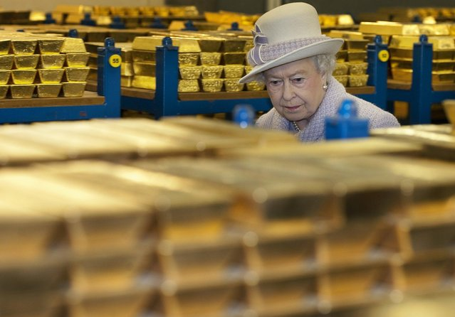 Queen Elizabeth II inspects gold reserves in a vault at the Bank of England in London, December 13, 2012. (Photo by Eddie Mulholland)