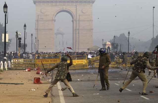Indian protesters and policemen throw stones at each other during a protest in New Delhi, on December 23, 2012. (Photo by Altaf Qadri/AP Photo)