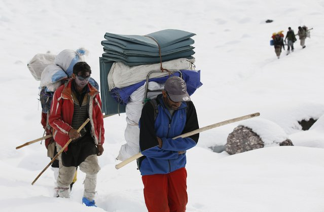Porters make their way through deep snow on the Baltoro glacier in the Karakoram mountain range in northern Pakistan September 8, 2014. While other parts of Pakistan and northern India were flooded, Concordia in the Karakoram mountain range was covered with a seasonally unusual amount of snow. (Photo by Wolfgang Rattay/Reuters)