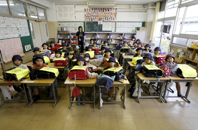 First grade students and their class teacher Teruko Takakusaki (in background) pose for a photo during their homeroom period at the end of the school day at Takinogawa Elementary School in Tokyo, Japan, September 18, 2015. (Photo by Toru Hanai/Reuters)