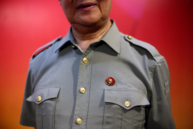 People's Liberation Army (PLA) officer Yao Werdong wears a pin with the portrait of late Chinese Chairman Mao Zedong during the opening of an exhibition of Mao related art in Beijing, China, September 8, 2016. (Photo by Thomas Peter/Reuters)
