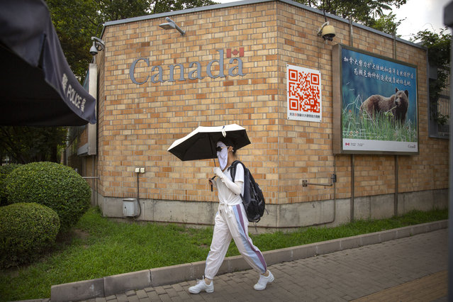 A woman wearing a face mask to help protect against the coronavirus walks past the Canadian Embassy in Beijing, Thursday, August 6, 2020. China has sentenced a Canadian citizen to death on charges of manufacturing the drug ketamine amid heightened tension between the two countries. (Photo by Mark Schiefelbein/AP Photo)