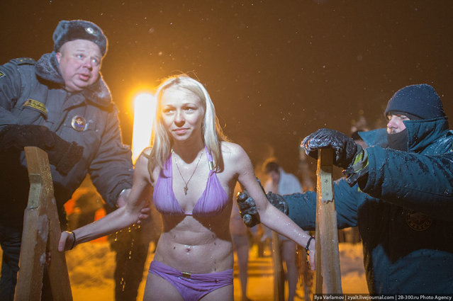 Police and rescuers help the young girl during mass ice bathing in Moscow on January 19, 2013. (Photo by Iliya Varlamov)