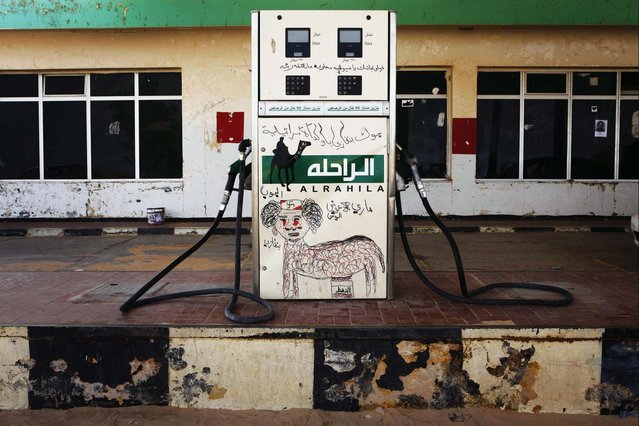 A fuel pump is defaced with a graffiti caricature of Muammar Gaddafi in the rebel-held town of Ajdabiyah, Libya March 31, 2011. (Photo by Finbarr O'Reilly/Reuters)
