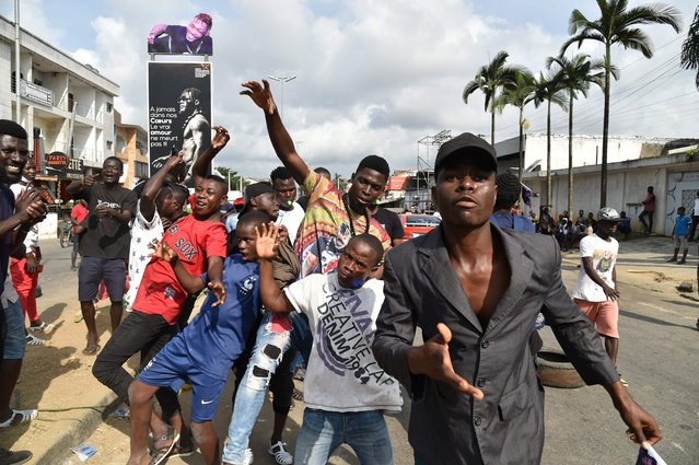 "Fans of Ivory Coast's ""coupé-décalé"" music star DJ Arafat gesture in Abidjan on August 12, 2020, as they gather to commemorate the one year mark after the death of Ivorian music star DJ Arafat at the site where he was killed in a motorcycle accident. (Photo by Issouf Sanogo/AFP Photo)"