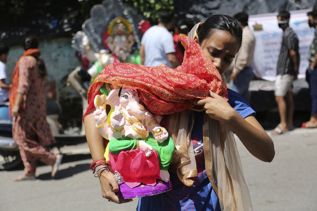 A devotee carries an idol of elephant-headed Hindu god Ganesha to take home for worship during reimposed weekend lockdown to prevent the spread of coronavirus in Jammu, India Saturday, August 22, 2020. (Photo by Channi Anand/AP Photo)