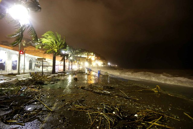 "This picture taken on November 4, 2014 in the French Riviera city of Nice, southeastern France shows the ""promenade des Anglais"" strewn with debris. Large waves broke against barriers at the harbour of Nice, as the French national meteorological service expanded to 16 the number of French departments on orange alert (the second highest weather warning), due to storms, heavy rain and a risk of flooding in some areas. (Photo by Valery Hache/AFP Photo)"