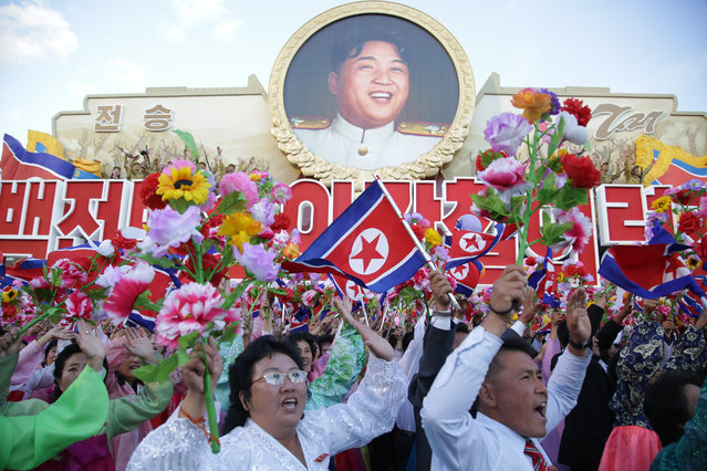 North Koreans cheer beneath an image of the late North Korean leader Kim Il Sung as they parade in Pyongyang, North Korea, Saturday, October 10, 2015. (Photo by Wong Maye-E/AP Photo)