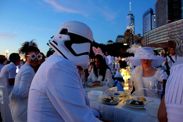 "A man wears a Star Wars Helmet as he attends the ""Diner en Blanc"" (Dinner in White) in Battery park New York on Septembre 15, 2016. The ""Diner en Blanc"" is a chic secret pop-up style picnic phenomenon originally started in France. (Photo by Kena Betancur/AFP Photo)"