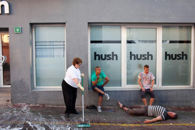 Derek from Hull (seated right), waits for an ambulance to arrive, with a man he discovered in distress in the West End area of San Antonio, Ibiza on June 28, 2013. (Photo by Peter Dench/Getty Images Reportage)