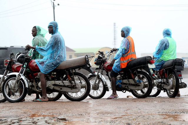 Motorcycle taximen wearing reflective rain jackets wait for passengers along a road during rainfall in Lagos, Nigeria, 09 September 2020. Rainfall prediction for Lagos for the rest of year is expected at an extreme volume, higher than the previous year, with a possible risk of flooding in the coastal areas and to the city's drainage infrastructure, according to a local media report. (Photo by Akintunde Akinleye/EPA/EFE/Rex Features/Shutterstock)