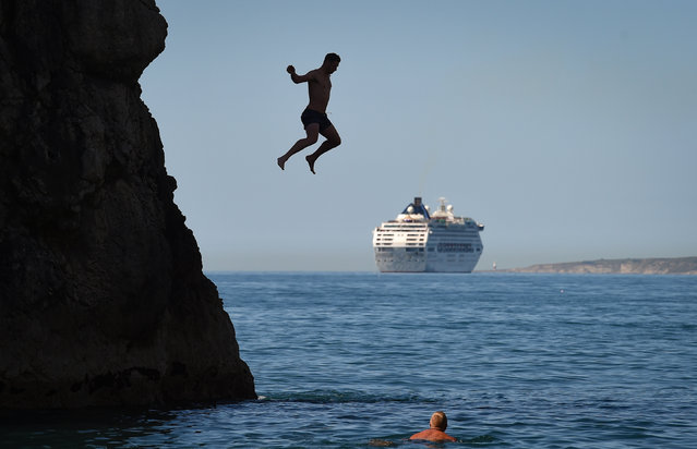 A man jumps from Durdle Door against the backdrop of a cruise ship as tourists enjoy the hot weather at Durdle Door beach on May 25, 2020 in West Lulworth, United Kingdom. (Photo by Finnbarr Webster/Getty Images)