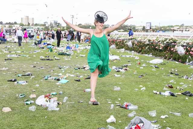 A women jumps over piles of rubbish during the Emirates Melbourne Cup Day held at Flemington Racecourse in Melbourne Australia, on November 4, 2014. (Photo by Asanka Brendon/Rex Features)