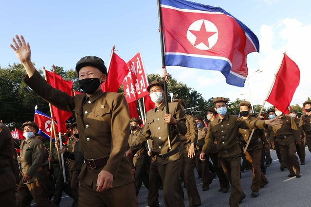 Political party members in support of the recovery efforts from typhoon damage parade at the plaza of the Kumsusan Palace of the Sun in Pyongyang, North Korea, Tuesday, September 8, 2020. A powerful typhoon damaged buildings and flooded roads in North Korea on Monday, the fourth spell of strong wind and rain to hit the country in just over a month. (Photo by Jon Chol Jin/AP Photo)