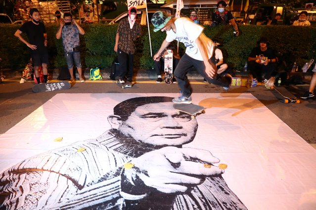 An anti-government demonstrator skates over an image of Thailand's Prime Minister Prayuth Chan-ocha during a Thai anti-government mass protest, on the 47th anniversary of the 1973 student uprising, in Bangkok, Thailand on October 14, 2020. (Photo by Athit Perawongmetha/Reuters)
