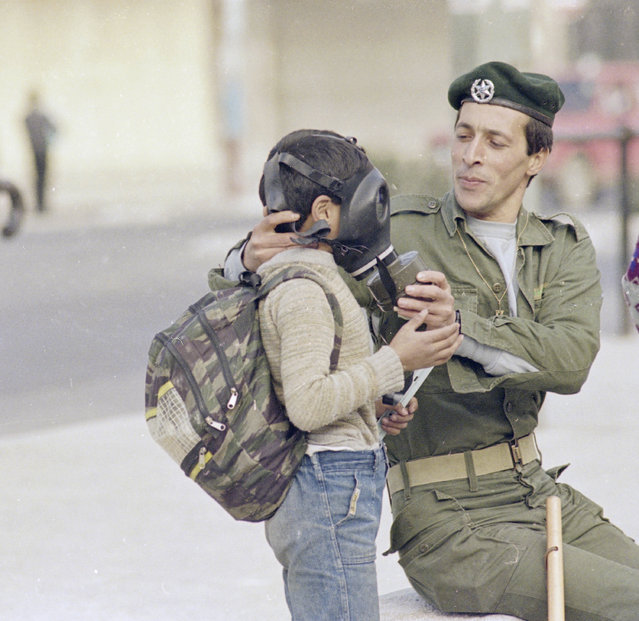 An Arab boy on the way home from school and who previously suffered the effects of teargas gets an assist from an Israeli border policeman in trying on a gas mask, January 11, 1988. (Photo by Max Nash/AP Photo)