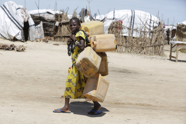 In this photo taken Sunday August 28, 2016 a girl displaced by Islamist Extremists carries empty plastic containers at a camp Maiduguri, Nigeria. Excited and fear-filled refugees from Boko Haram piled onto buses with pathetic bundles of belongings, returning after two years to homes that have been torched, wells and crops destroyed, livestock looted and fields that may not be safe from the Islamic insurgents. (Photo by Sunday Alamba/AP Photo)