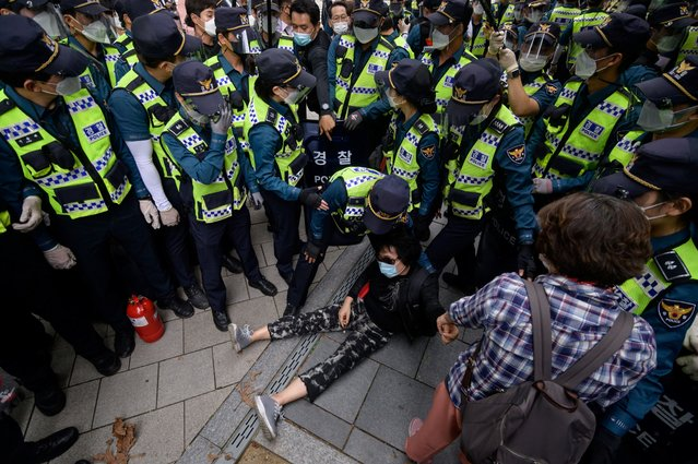 A conservative anti-government protester sits on the ground following an altercation with police during an attempted rally in the central Gwanghwamun district of Seoul as South Korea marks 'Foundation Day' on October 3, 2020. Conservative groups had planned to hold anti-govenment rallies throughout central Seoul, which were banned by police due to concerns over the spread of the covid-19 coronavirus. (Photo by Ed Jones/AFP Photo)