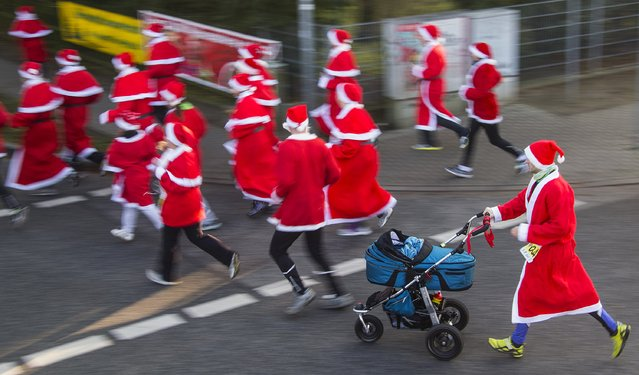 A runner dressed as Father Christmas pushes a baby stroller during the Nikolaus Lauf (Santa Claus Run) in the east German town of Michendorf, southwest of Berlin December 7, 2014. (Photo by Hannibal Hanschke/Reuters)