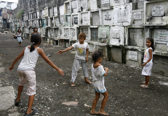 Children play inside a cemetery in Manila, October 21, 2008. (Photo by Cheryl Ravelo/Reuters)