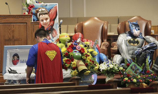 Dale Hall, dressed as Superman, stands before the casket during a superhero-themed funeral service for his brother, Jacob Hall at Oakdale Baptist Church on Wednesday, October 5, 2016, in Townville, S.C. A 14-year-old boy killed his own father, then drove to Townville Elementary and fired on two children and a teacher as recess began. Jacob died Saturday. (Photo by Ken Ruinard/The Independent-Mail via AP Photo)