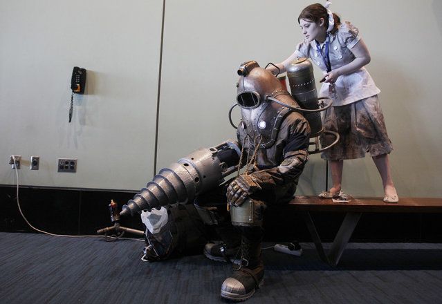 Aly Ilyadias helps Will Patriquin with his costume, both of them dressed as characters from the video game BioShock, at the PAX East gaming convention in Boston, Massachusetts, on March 23, 2013. (Photo by Jessica Rinaldi/Reuters /The Atlantic)
