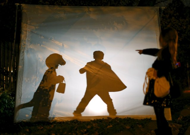 Trick-or-treaters play behind a scrim with a strobe light during Halloween night in Silver Spring, Maryland, October 31, 2015. (Photo by Gary Cameron/Reuters)